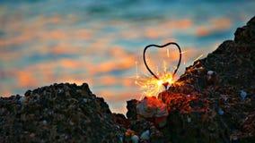 Bengala en forma de corazón en la costa rocosa delante de la agua de mar de movimiento lento con los puntos ligeros de la puesta