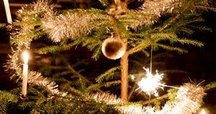 Bengala y vela que brillan intensamente en árbol de navidad metrajes