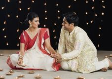 Bengali couple lighting oil lamps Royalty Free Stock Images