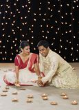 Bengali couple lighting oil lamps. And smiling stock photo