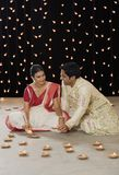 Bengali couple lighting oil lamps Stock Images
