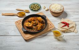 Bengali fish curry and set Indian spices with basmati rice on wooden table. stock image