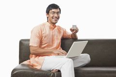 Bengali man holding a credit card and using a laptop Royalty Free Stock Images