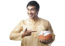 Bengali man pointing towards a pot of rasgulla Royalty Free Stock Images
