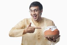 Bengali man pointing towards a pot of rasgulla Stock Photography