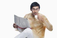 Bengali man reading a newspaper and having tea Royalty Free Stock Photos