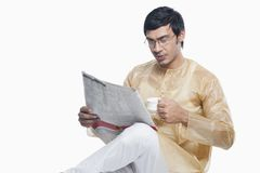 Bengali man reading a newspaper and having tea Stock Image