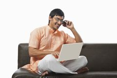 Bengali man using a laptop and talking on the mobile phone on th Stock Photography