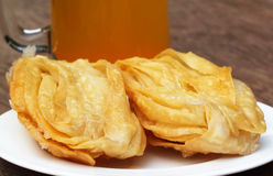 Bengali treats named as GOJA. On a plate with juice royalty free stock photos
