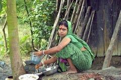 Bengali woman during dish washing outside poor hut Royalty Free Stock Photos