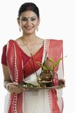 Bengali woman holding a puja thali. Portrait of a Bengali women holding a puja thali and smiling royalty free stock photos