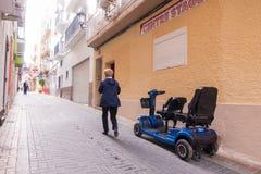 Benidorm, Espanha - 29 de janeiro de 2018: O turista gosta de usar 'trotinette's contratados da mobilidade na rua de Benidorm, Es imagens de stock