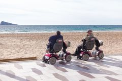 Benidorm, Spain - January 14, 2018: Seniors on mobility scooters looking to the sea in Benidorm, Spain.  royalty free stock photography