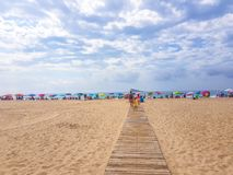 Benidorm, Spain; 12 july 2018: Entrance to the beach by the wooden walkway with umbrellas, tourists and sea background royalty free stock photo
