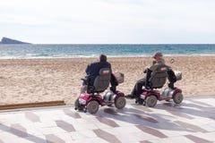 Benidorm, Spanien - 14. Januar 2018: Senioren auf den Mobilitätsrollern, die zum Meer in Benidorm, Spanien schauen Lizenzfreie Stockfotografie