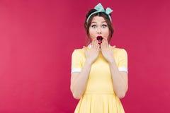 Benieuwd geweest pinup meisje in gele kleding met geopende mond stock foto's