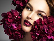 Benieuwd zijnd meisje in bloemen met make-up stock foto's