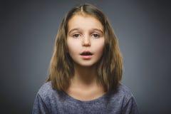 Benieuwd zijnd meisje Close-upportret van knap kind op grijze achtergrond royalty-vrije stock afbeelding