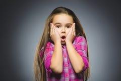 Benieuwd zijnd meisje Close-upportret van knappe tiener op grijze achtergrond royalty-vrije stock afbeelding
