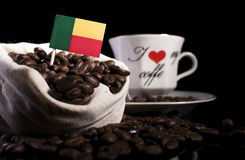 Benin flag in a bag with coffee beans isolated on black. Background stock photography