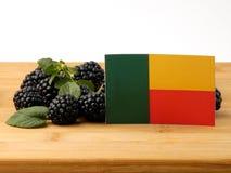 Benin-Flagge auf einer Holzverkleidung mit den Brombeeren lokalisiert auf einem whi lizenzfreie stockfotos