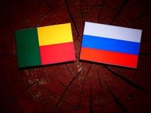 Benin-Flagge mit russischer Flagge auf einem Baumstumpf stockfotos
