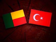 Benin-Flagge mit türkischer Flagge auf einem Baumstumpf lizenzfreie stockfotografie