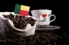 Benin vlag in een zak met koffiebonen op zwarte worden geïsoleerd die stock fotografie