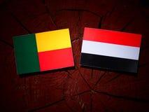 Benin vlag met Yemeni vlag op een boomstomp stock foto