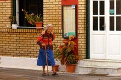 BENITSES, GRÉCIA, O 19 DE OUTUBRO DE 2018, uma senhora idosa agradável toma uma caminhada foto de stock royalty free