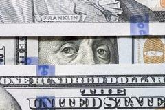 Benjamin Franklin ögon mellan hundra dollarsedelnärbild Ögon av Benjamin Franklin som håller ögonen på från bunt av pengarfönstre fotografering för bildbyråer