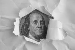 Benjamin Franklin-gezicht het letten op door het gescheurde document Stock Foto