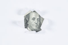 Benjamin Franklin macro peeking through torn white paper. Stock Photography
