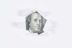 Benjamin Franklin makro som kikar till och med sönderriven vitbok Arkivbild