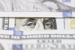 Benjamin Franklin`s eyes between hundred dollar banknotes close-up. Eyes of Benjamin Franklin watching from stack of money window. S royalty free stock photography