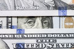 Benjamin Franklin`s eyes between hundred dollar banknotes close-up. Eyes of Benjamin Franklin watching from stack of money window. S stock image