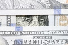 Benjamin Franklin`s eyes between hundred dollar banknotes close-up. Eyes of Benjamin Franklin watching from stack of money window. S royalty free stock image