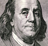 Benjamin Franklin`s portrait on one hundred dollar bill. Franklin portrait with tears of blood. Franklin crying. Royalty Free Stock Image