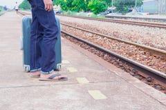 Benmannen av loppet satte jeans står och resväskaväntandrevet i stationsslingaplattform med kopieringsutrymme Royaltyfri Bild