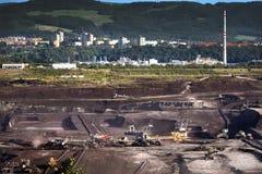 Benna da scavo gigante che porta via gli strati di terra Immagine Stock