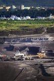 Benna da scavo gigante che porta via gli strati di terra Immagini Stock