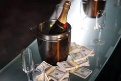 Benna di champagne vicino a contanti Fotografia Stock