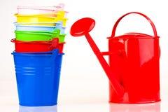 Benne e latta di innaffiatura colorate fotografie stock