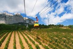 Benne suspendue dans les montagnes au-dessus des champs photos stock