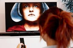 Benon, Frankreich - 30. Dezember 2018: Frau, die eine Fernsehdirektübertragung und die Geschichte des Handmaids aufpassen hält Di lizenzfreies stockbild