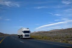 Bens pesados no trânsito através das estradas Tarred Imagem de Stock