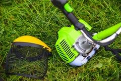 Bensingräsklippningsmaskin och skyddande maskering på gräset Arkivbilder