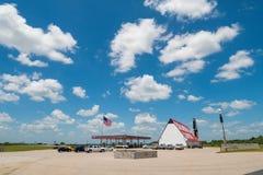 Bensinstation i USA med massor av brett öppet utrymme och amerikanska flaggan som blåser i vind Arkivfoto