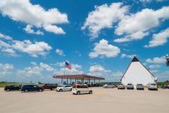 Bensinstation i USA med massor av brett öppet utrymme och amerikanska flaggan som blåser i vind Arkivfoton
