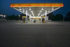 Bensinstation med ljus på och kortkort-marknaden på skymning i centrala GUMMIN Royaltyfria Foton